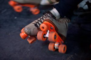 Close-up of person's feet wearing a leather pair of roller skates at Rainbow Roller Rink