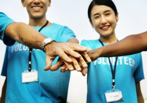 """4 people in a circle  wearing """"volunteer"""" shirts putting their hands in the middle"""