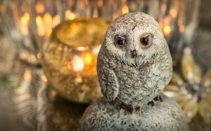 Small snow owl ornament in front of out of focus holiday decorations