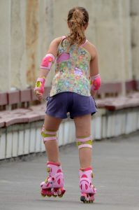 Girl skating outside wearing skating pads