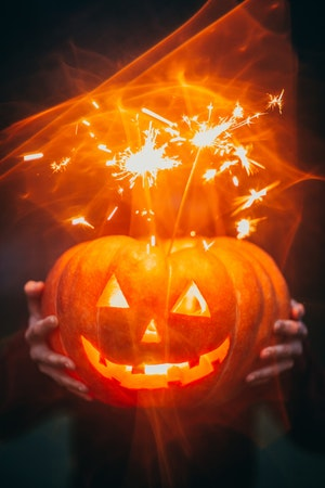 Hands holding jack o'lantern with sparklers