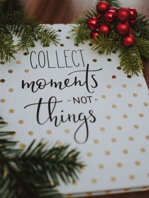 "Photo of sign saying ""Collect moments, not things"" with evergreen and berries"