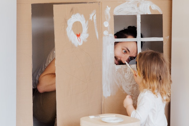 Dad and small daughter playing in makeshift playhouse