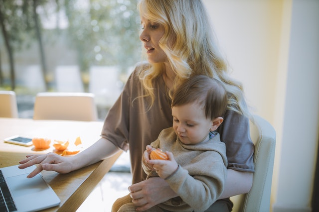 Blonde woman working from home while holding small child
