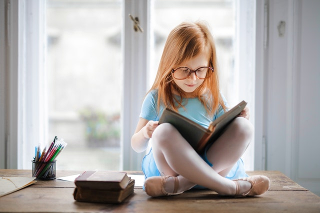 Ginger girl reading book in front of window