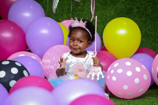 Cute baby girl surrounded by birthday balloons