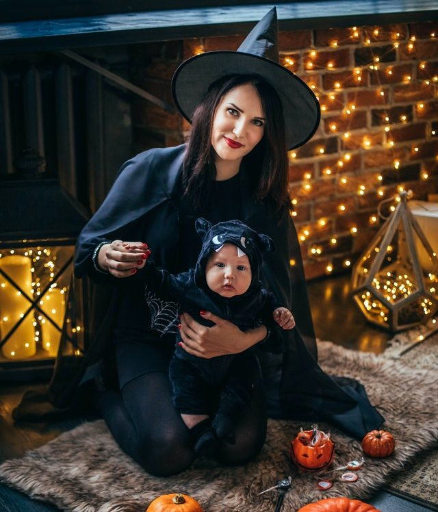 mom dressed as witch holding cute baby in bat costume