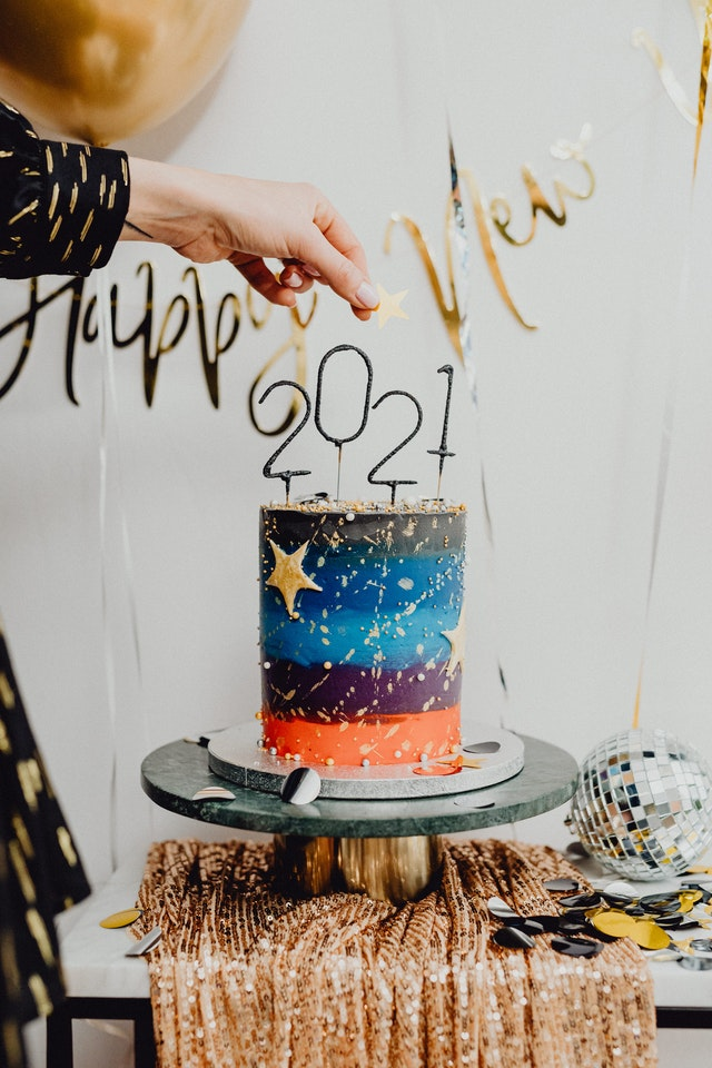 Hand holding gold star over a cylindrical cake with 2021 candles