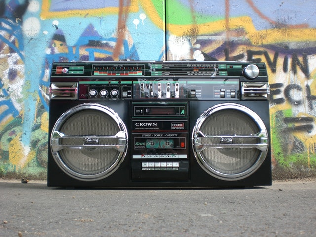 Boombox in front of graffitied wall