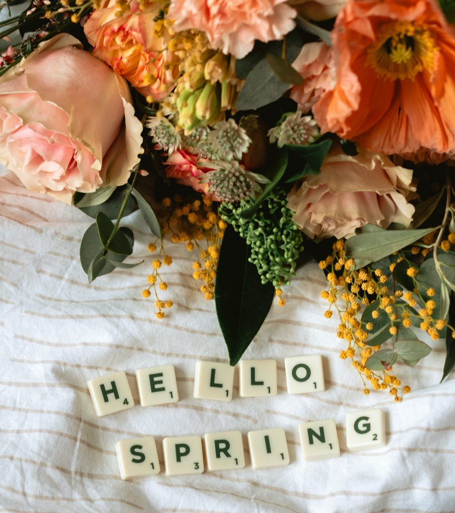 """Flowers with letter tiles spelling """"hello spring"""""""