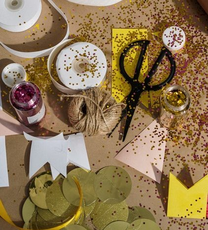 Woman sitting on floor with craft items covered in glitter