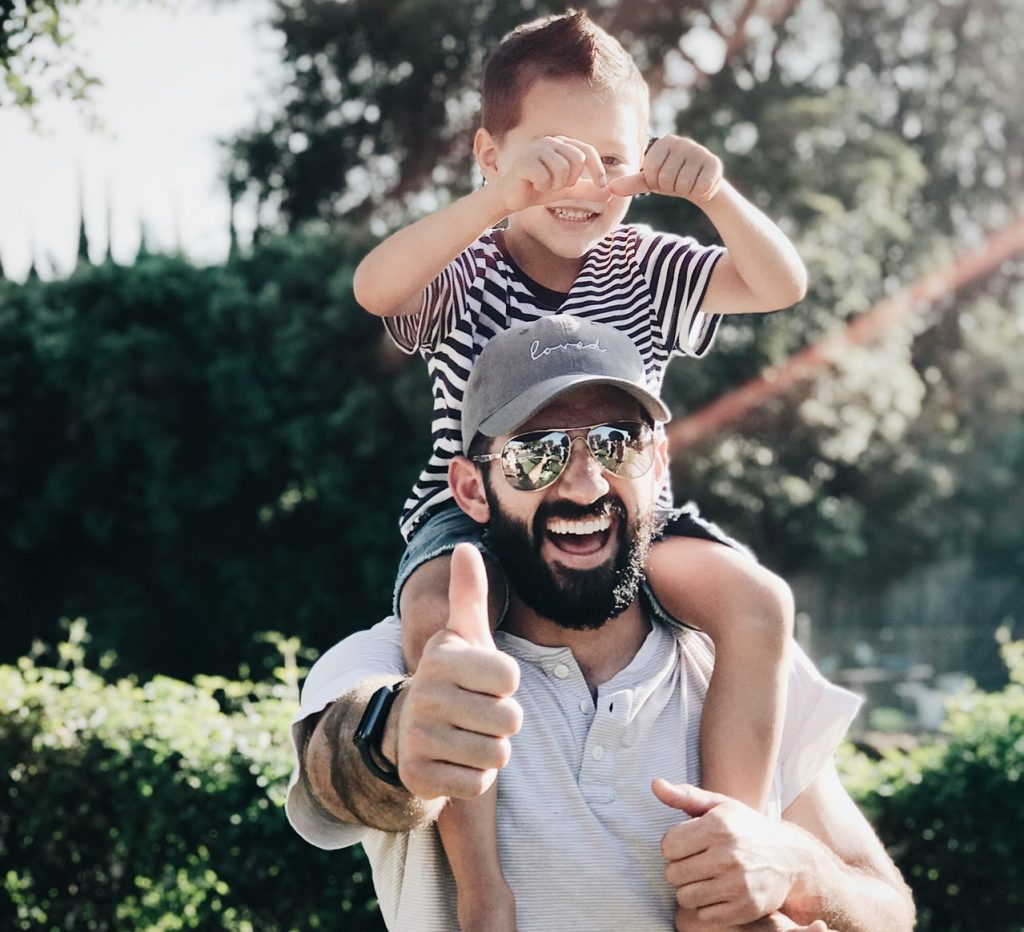 Smiling dad carrying happy kid on his shoulders on a sunny day
