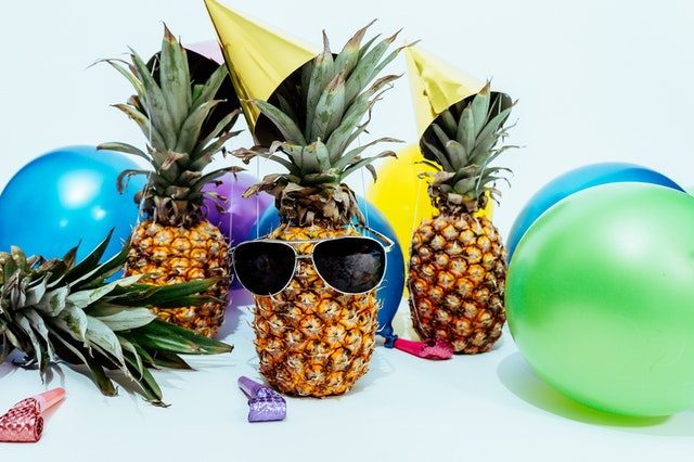 Still life of pineapples, party hats, noisemakers, and balloons