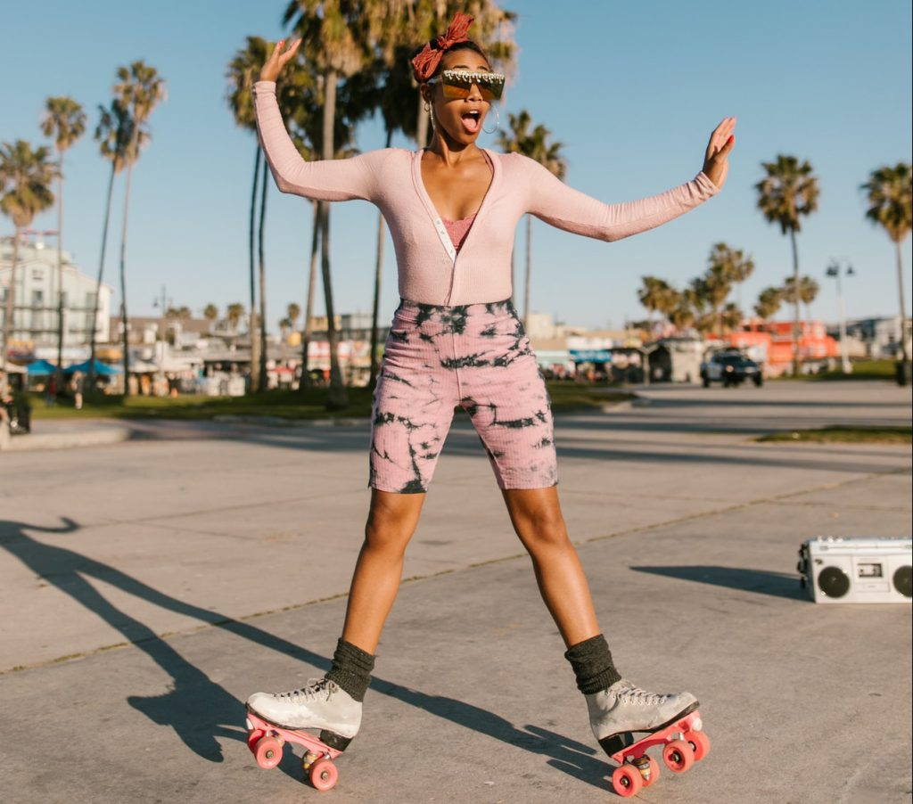 Woman in colorful outfit striking a pose on roller skates
